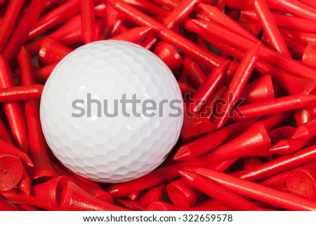 White golf ball lying between red wooden golf tees - stock photo