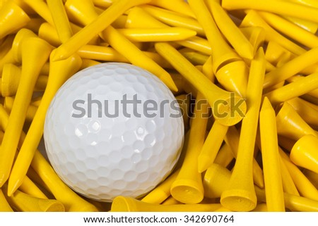 White golf ball lying between yellow wooden golf tees - stock photo