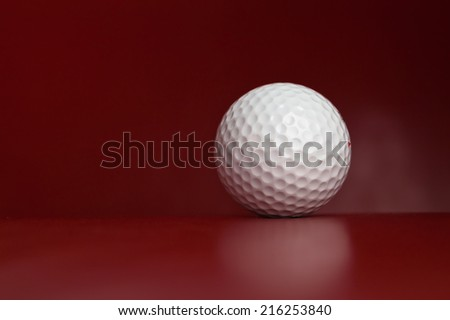 White golf ball lying on red leather green - stock photo