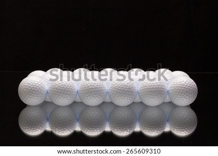 White golf balls on a glass plate - stock photo