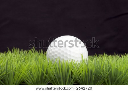 white golfball on green fairway, isolated on black background - stock photo