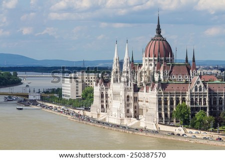 White Gothic building of the Hungarian Parliament in Budapest. The building is located on the Danube River in the background of hills and blue sky - stock photo