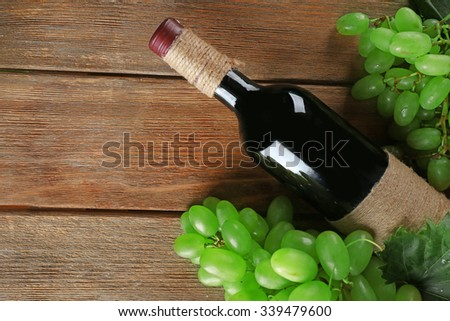 White grape with wine bottle on wooden background - stock photo