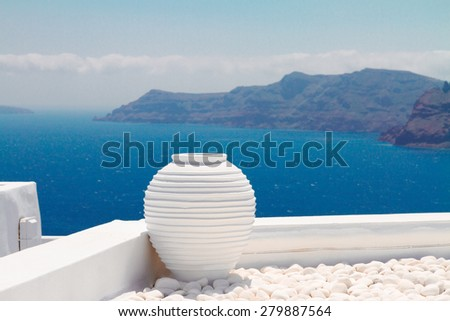 white greek amfora against volcano caldera and sea at sunny day, beautiful details of Santorini island, Greece - stock photo