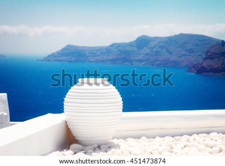 white greek amfora against volcano caldera and sea at sunny day, beautiful details of Santorini island Greece, toned - stock photo