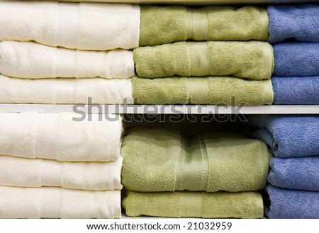 White, green, and blue towels on a shelf in a retail store or linen closet