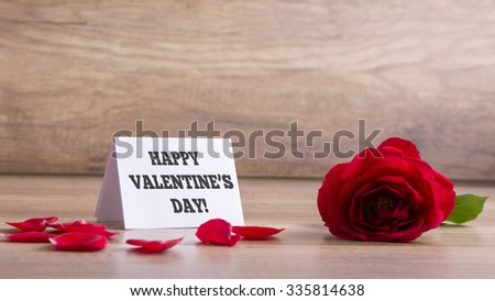 White greeting card with a Happy Valentines day sign next to a beautiful red blooming rose on a wooden desk scattered with rose petals. - stock photo