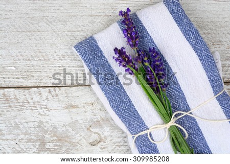 white grey old white wooden shelves background with empty copy space and lavender flowers and blue napkin towel decoration - stock photo