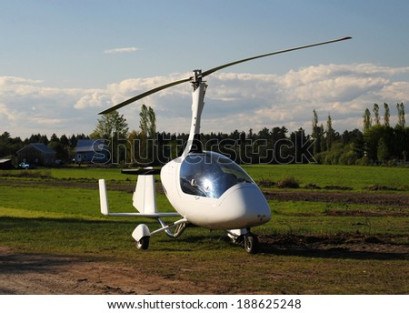 White gyroplane parked on the private airfield in the sunny day - stock photo
