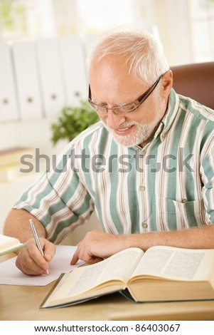 White hair pensioner sitting at desk, writing letter at home, smiling.? - stock photo