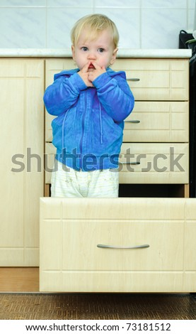 white haired little boy in the kitchen cabinet