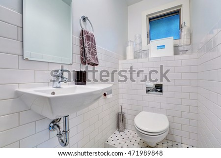 White half bathroom interior with tile wall trim. There is a window, toilet and washbasin with mirror. Northwest, USA