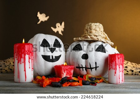 White Halloween pumpkins and candles on wooden table on dark color background - stock photo