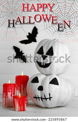 White Halloween pumpkins, candles, on white wooden background