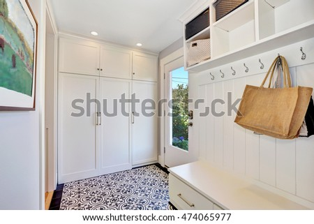 White hallway storage cabinet with hangers and closet. Also white and black floral patterned tile floor in vintage style. Northwest, USA