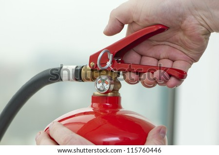 white hand presses the trigger fire extinguisher