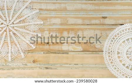 White handmade crochet doilies over wooden background - stock photo