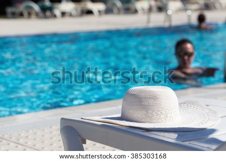 White hat left by a swimming pool with woman swimming in it.