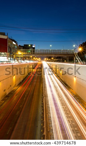 white headlights and red tail lights disappearing to the tunnel  under the junction in Bangkok Thailand