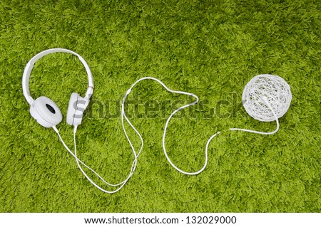 White headphones and ball made of thread, on the green carpet.