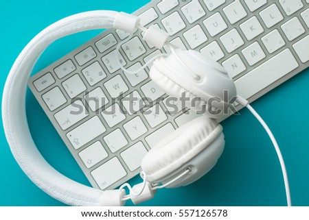 White headphones and computer keyboard on blue background. Top view.