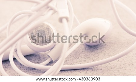 White headphones lying on stone table in close up. Concept of audio, sound or mobile accessory.