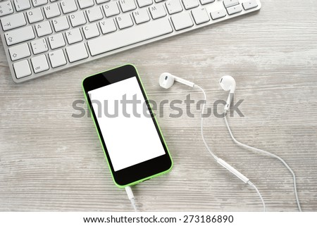White headphones with the phone and keyboard closeup - stock photo