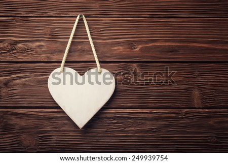 White heart hanging over wooden vintage background - stock photo