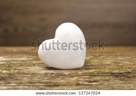white heart of stone on wood - stock photo