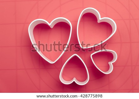White heart shape cookie cutters on baking mat