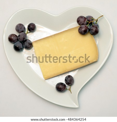 White heart shaped plate with french cheese and raisin grapes