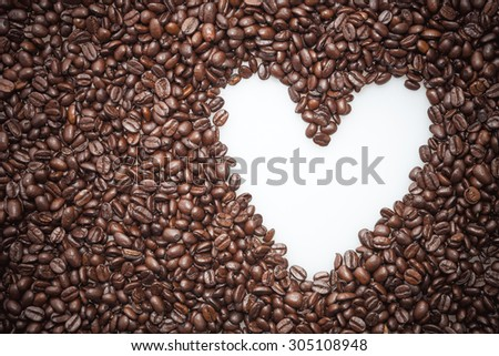 White heart symbol in coffee beans - stock photo