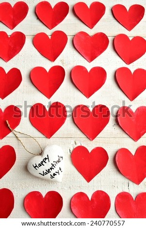 "White heart ""Valentines day"" message ornament on red heart paper cut out background"