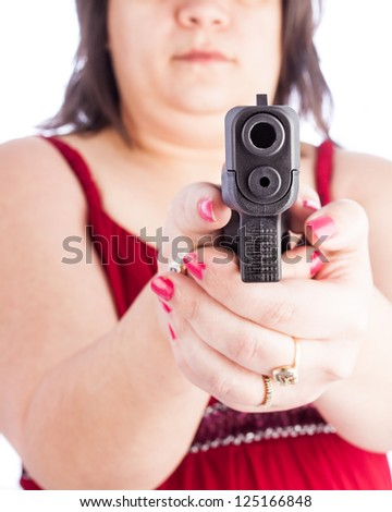white hispanic woman holding a handgun pointed at the screen. Shallow depth of field with focus on the barrel. Red dress with an average looking woman protecting herself with a weapon. - stock photo