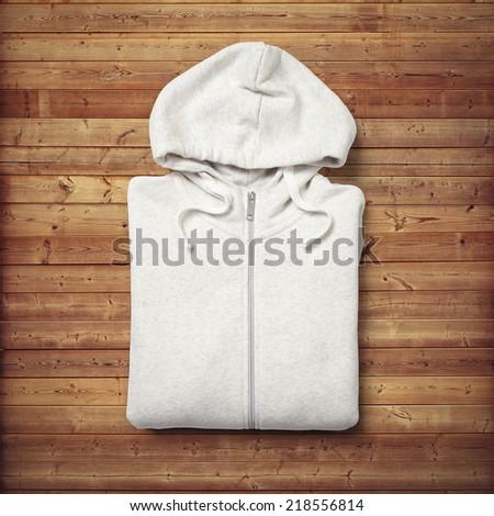 White hooded sweater on wood background - stock photo