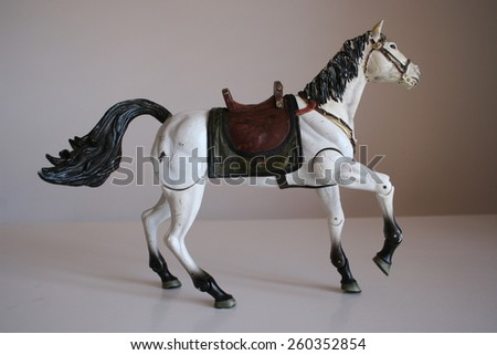 White horse toy with a saddle on it taking his first step forward - stock photo