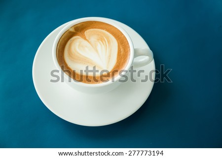 White hot coffee cup on blue leather desk - stock photo