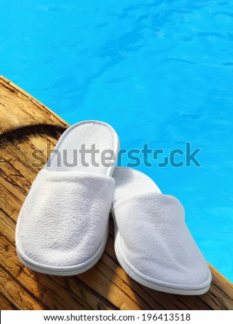 White hotel / home/ spa / wellness slippers on wood with swimming pool background with space for text - summer time  - stock photo