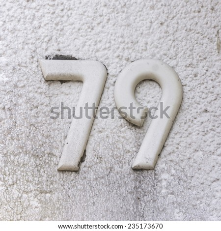 White house number seventy nine on a stucco wall - stock photo