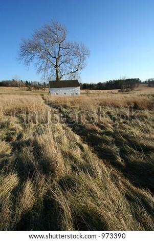 White house on a prairie with a dirt path leading up to it - stock photo