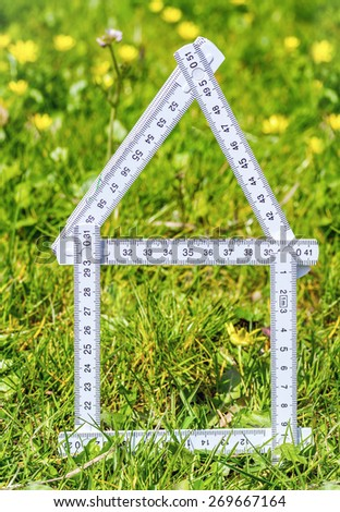 White house outline in the grass for real estate - stock photo