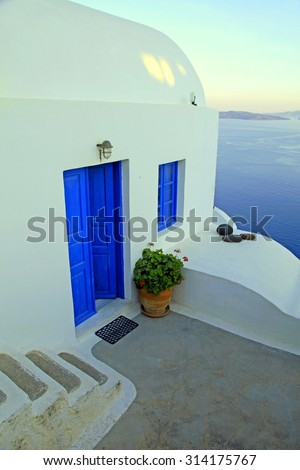 White house with blue windows and door in traditional village Oia on Santorini island, Greece. Sunset light, toned image