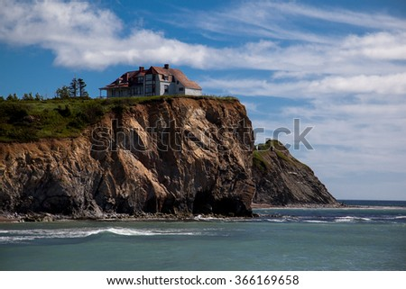 White house with red roof on cliff near Perce Rock in the Gaspe, Quebec, Canada