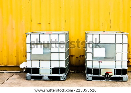 White IBC container in front of a yellow cargo container - stock photo