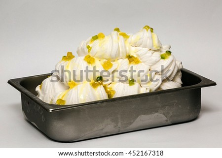 White ice cream with candied peel in the metal tray on white background