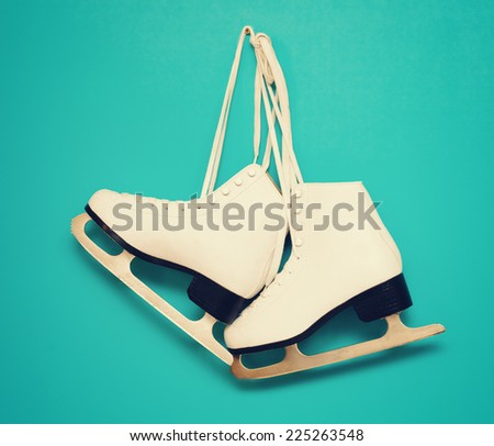 white ice skates for figure skating, hanging on a blue background, with instagram effect - stock photo