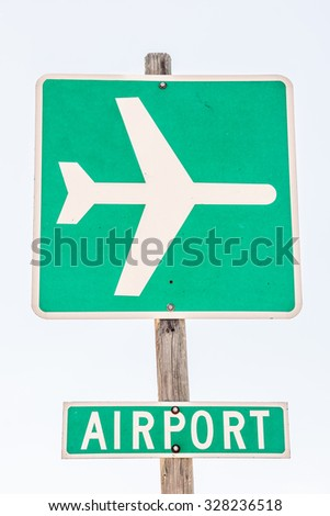 White icon of an airplane and the word airport on green backgrounds to let drivers know where to turn - stock photo
