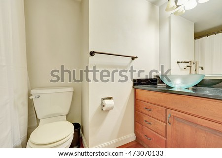 White interior of bathroom with wooden vanity and glass blue washbasin. Northwest, USA