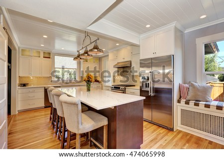 White interior of kitchen room with bar style kitchen island and stools, stainless steel double fridge and view of window seat. Northwest, USA