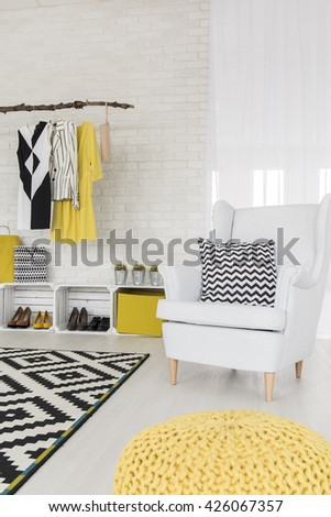 White interior with white armchair, hanging clothing rack and pattern details